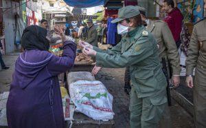 Une Caïda qui essaye de convaincre une veille dame dans un souk au Maroc